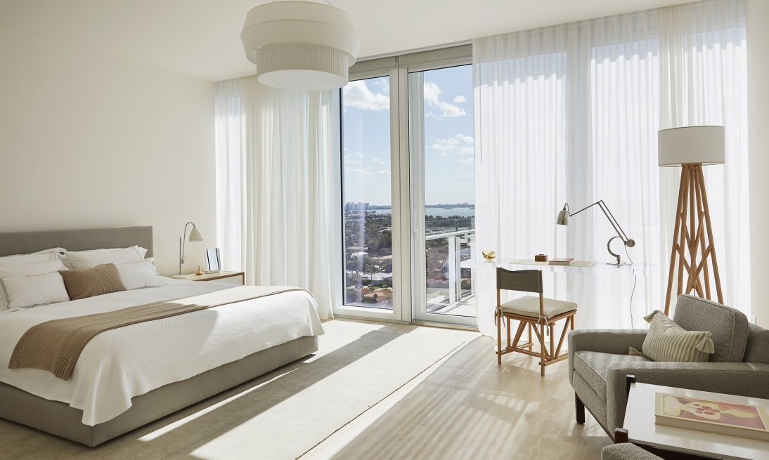 Neutral bedroom with city window view. Lucite desk with wood chair and floor lamp.